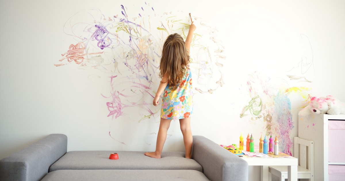 a child experiencing flow through painting on the walls - tots to teens