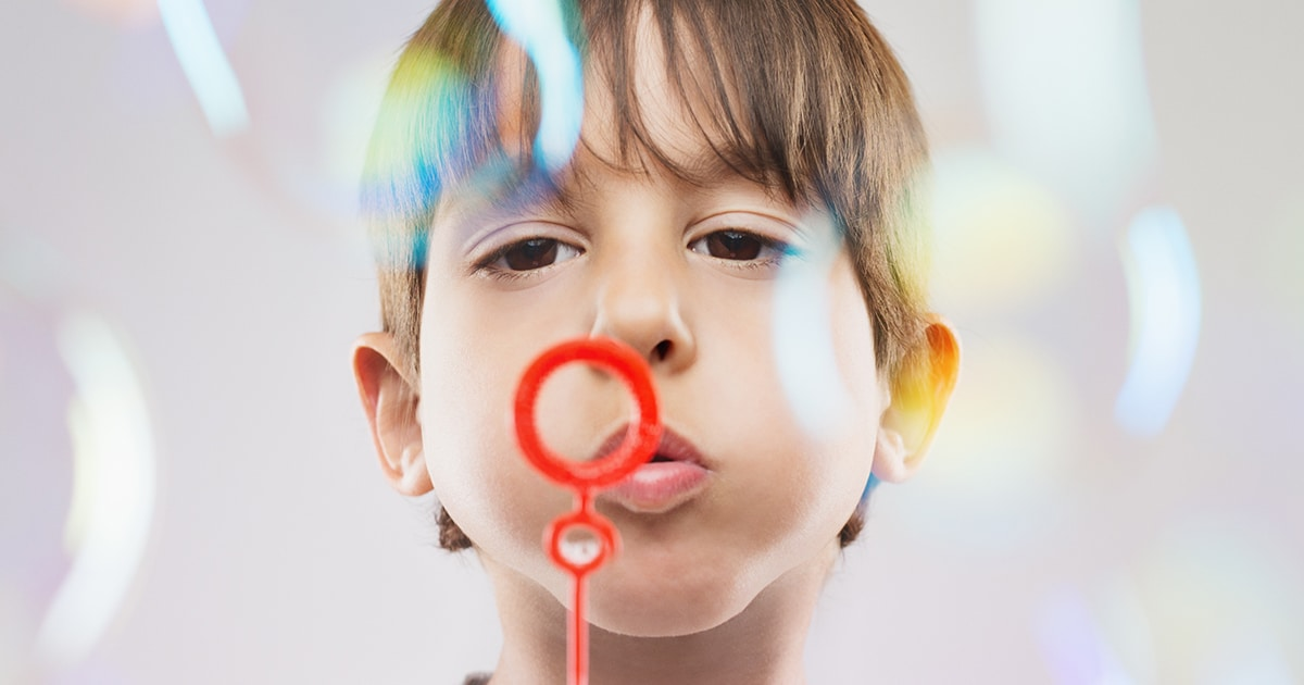 a child blowing bubbles and practicing mindfulness - tots to teens