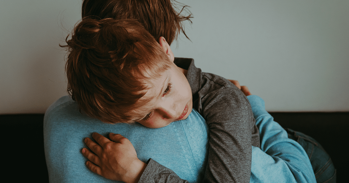 child being comforted by his mother   due to frightening world events - tots to teens