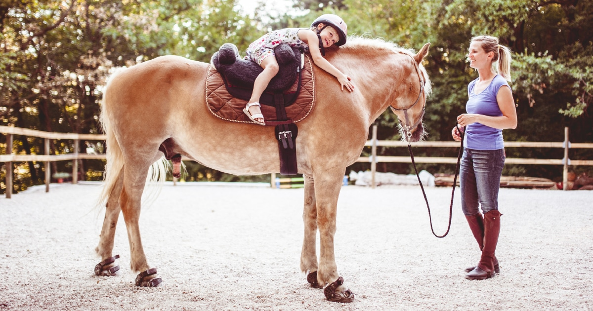 a young girl hugging a horse - tots to teens