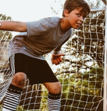 young boy defending football goal