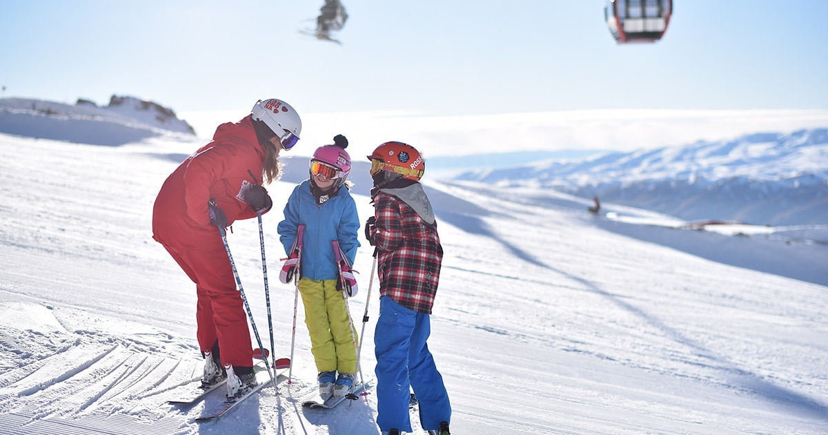 three people on skis on a snowy hill