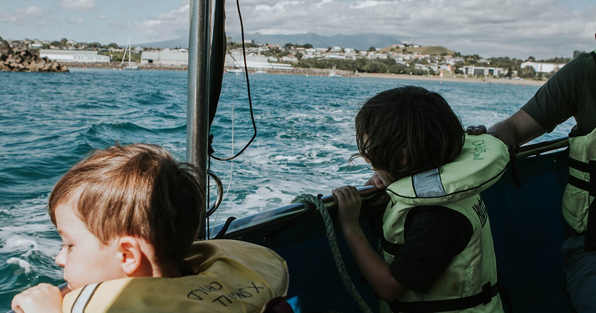 two boys in life jackets on a boat