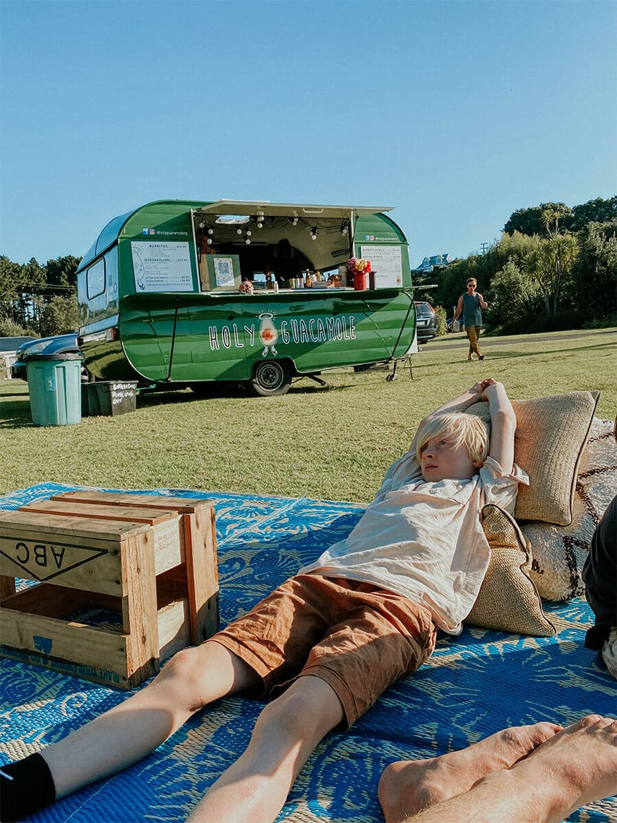 boy relaxing in front of a green food truck