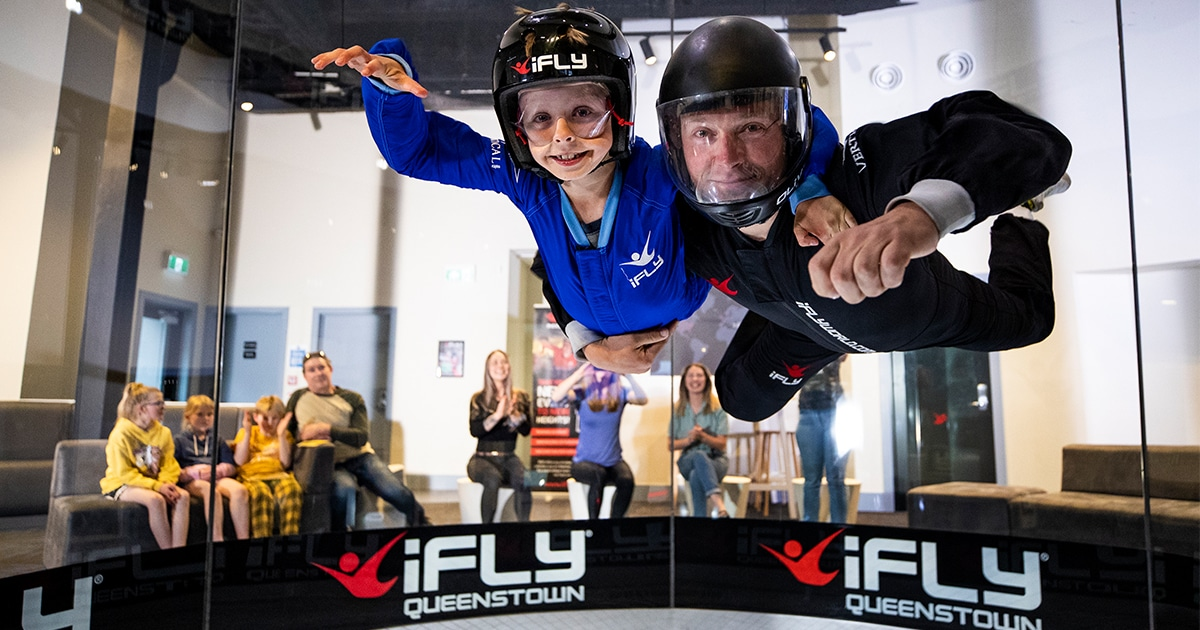 two people levitating at an indoor skydiving location