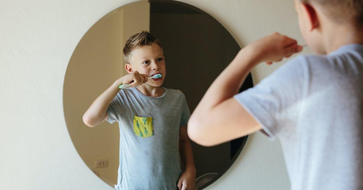 blonde boy brushing his teeth