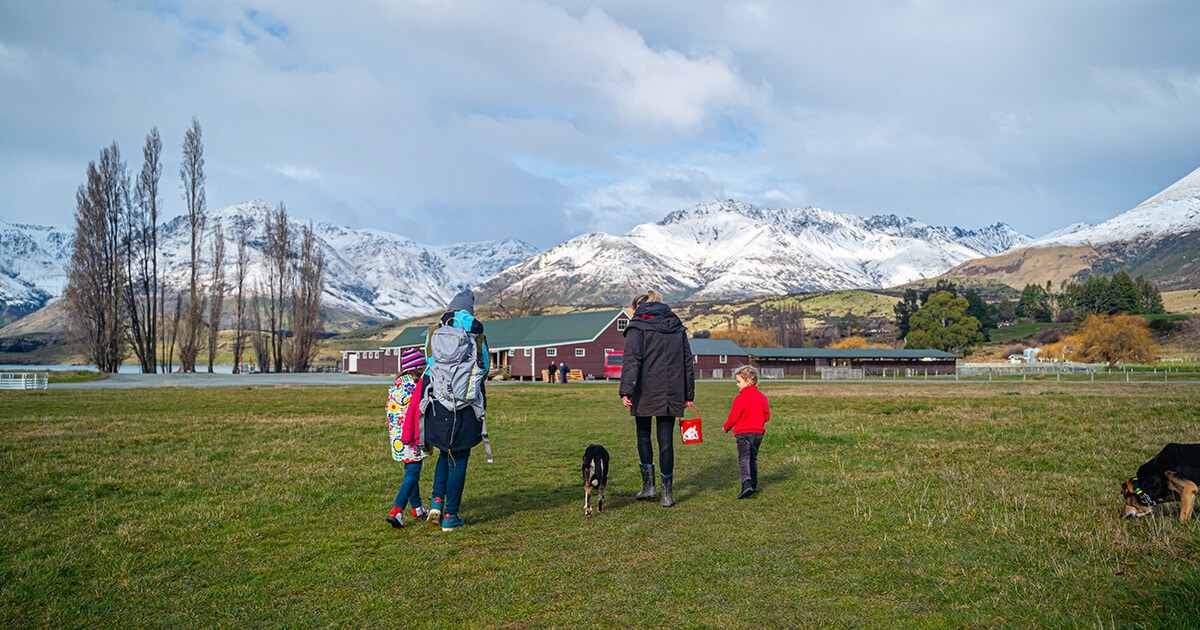A family and a dog walking on a farm with mountains in the background